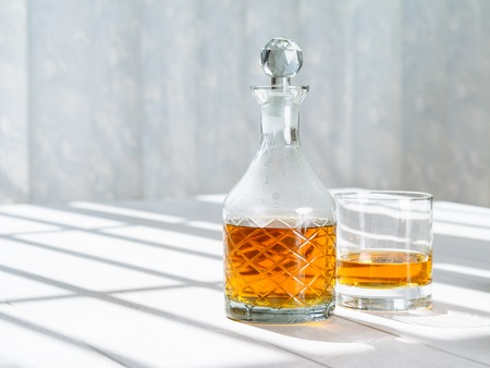 cocktail drinks: Photo of a whisky decanter and rocks glass on a table by a window. Stock Photo