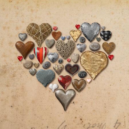 빈티지 종이 배경 위에 심장의 모양으로 구성 돌, 금속, 나무로 만든 하트 모양의 물건의 사진.
