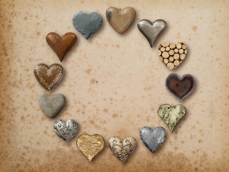 Photo of metal, wood and stone heart-shaped things organized in a circle over vintage paper background. photo