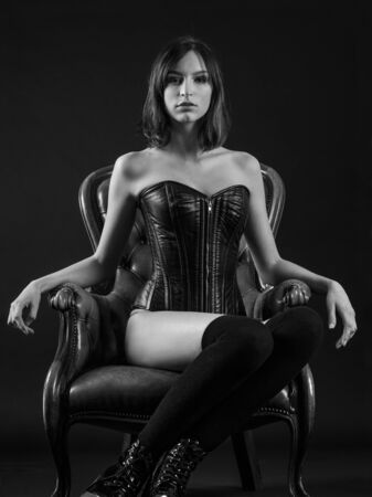 Photo of a beautiful young woman sitting on a leather chair wearing a black leather corset and stockings.