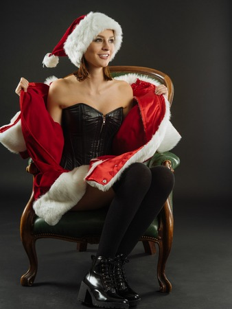 Photo of a beautiful woman in a leather corset opening her Santa coat and smiling. photo