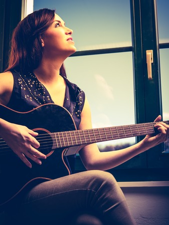 heavily: Photo of a beautiful brunette female playing an acoustic guitar by the window. Heavily filtered.