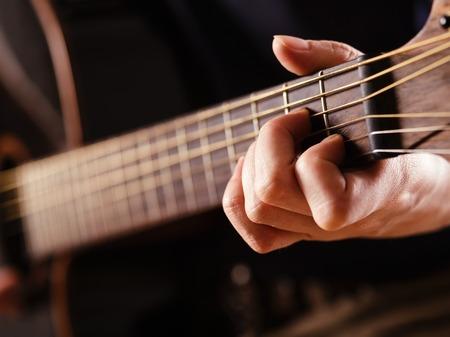 guitarra acustica: Foto de una mujer tocando una guitarra acústica con extrema profundidad superficial de campo con el foco en la mano y pala.
