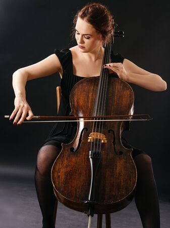 Photo of a beautiful woman playing an old cello.
