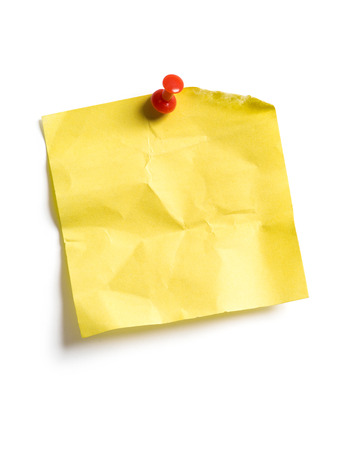 Photo of an isolated yellow sticky note pinned to a white background. photo