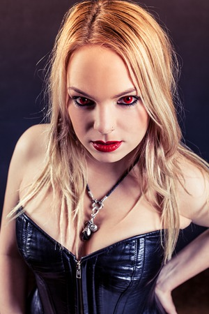 goth girl: Photo of a woman with red eyes and red lipstick wearing a black leather corset.  Harsh lighting and filtered for scarier feel.