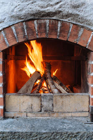 outdoor fireplace: Photo of an outdoor brick fireplace with a fire blazing inside.