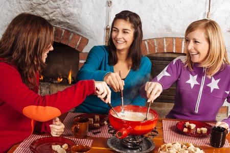 Photo of three beautiful females dipping bread into the melted cheese in a fondue pot. photo