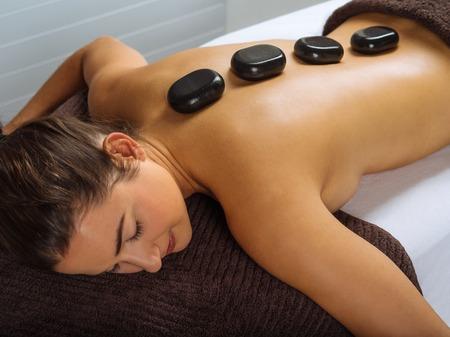 Foto de una mujer joven que miente en un spa que tiene un tratamiento con piedras calientes. Centrarse en las dos primeras piedras. Foto de archivo