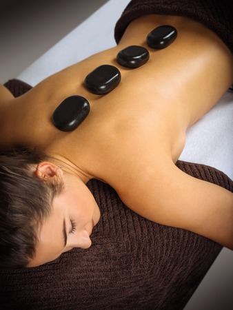 Photo of a young woman lying in a spa having a hot stone treatment. Focus on the first two stones.