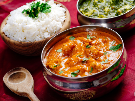 across: Photo of an Indian meal of Butter Chicken, rice and Saag Paneer. Focus across the Butter Chicken bowl.