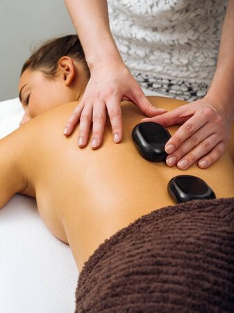 masseuse: Photo of a young woman lying in a spa having a hot stone treatment. Focus on the hands of the masseuse.
