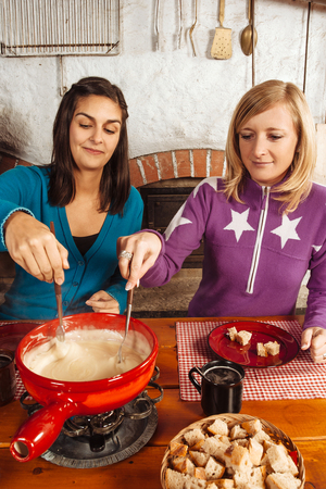swiss culture: Photo of two beautiful women dipping bread into the melted cheese in a fondue pot.