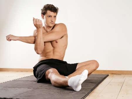 hombros: Foto de un hombre joven que estira sus attractuive músculos del hombro mientras se está sentado en la estera de ejercicio.