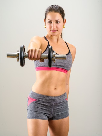shoulders: Photo of a pretty woman doing shoulder exercises with a dumbbell. Stock Photo