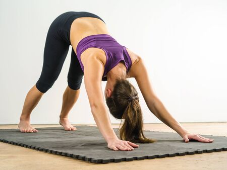 floor mat: Photo of a healthy young woman doing the downward dog yoga position on a black floor mat.