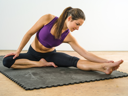 Photo of a beautiful woman stretching on the floor sitting on a mat.
