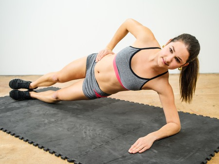 Photo of a young woman in her twenties doing a side elbow plank.