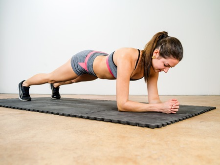plank: Photo of a beautiful young woman exercising and doing an elbow plank to strengthen her stomach muscles.