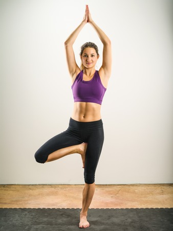 tree position: Photo of a young beautiful woman exercising and doing the Yoga tree position. Stock Photo