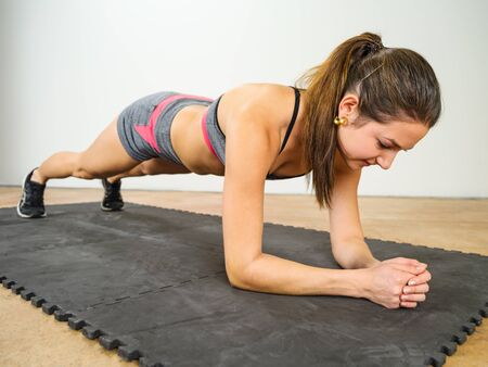 stretches: Photo of a beautiful young woman exercising and doing an elbow plank to strengthen her stomach muscles.