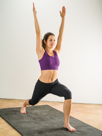 floor mat: Photo of a healthy young woman doing the warrior yoga position on a black floor mat.