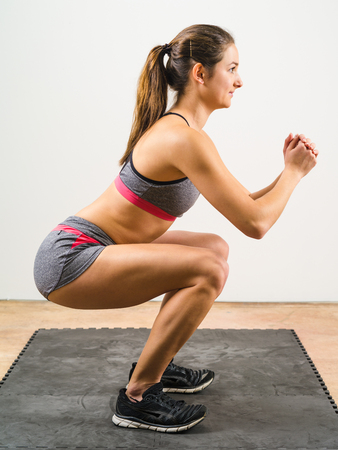 floor mat: Photo of a young woman exercising and doing a isometric squat on a black floor mat.