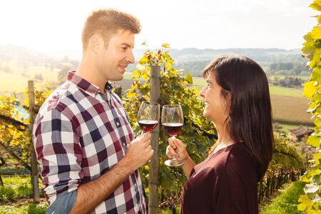 Photo of a young couple tasting and drinking wine in a vineyard. photo