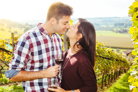 Photo of a young couple kissing and drinking wine in a vineyard. photo