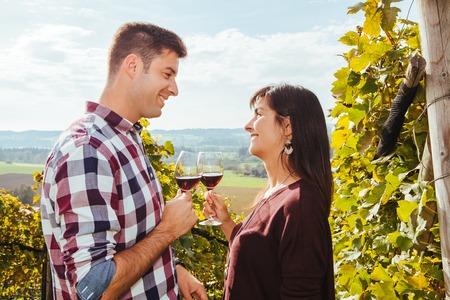 tomando vino: Foto de una joven pareja de degustación y beber vino en un viñedo.