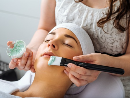 spa woman: Photo of a young beautiful girl receiving a green facial mask in spa beauty salon.