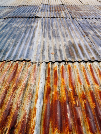 damaged roof: Photo of a rusty corrugated metal roof at an angle.