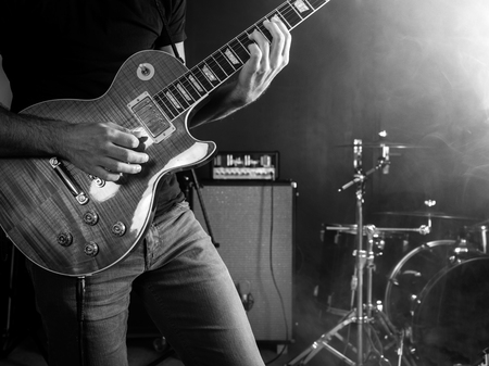 Photo of a guitar player playing on stage done in black and white.