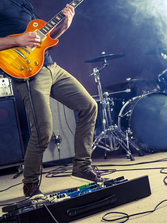 amps: Photo of a guitar player playing on stage.