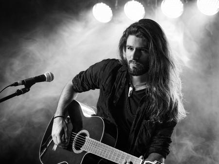 긴 머리와 조명과 콘서트 분위기로 무대에 어쿠스틱 기타를 연주하는 수염을 가진 젊은 남자의 사진.