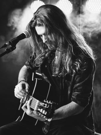 capelli lunghi: Foto di un giovane uomo con i capelli lunghi e un canto barba e suonare una chitarra acustica sul palco con le luci e l'atmosfera da concerto.