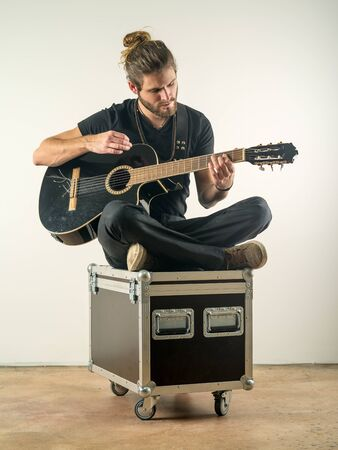 man with long hair: Photo of a young attractive man with long hair and beard sitting on a flight case and playing an acoustic guitar.