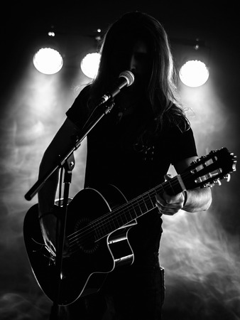 Photo of a backlit young man with long hair in silhouette playing an acoustic guitar on stage. Foto de archivo