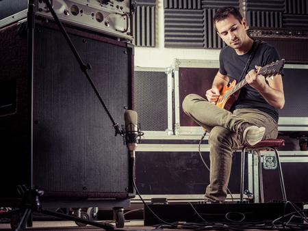 Foto von einem Mann in den späten 20er Jahren in einem Aufnahmestudio sitzt seine Gitarrenspuren aufnehmen.