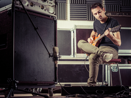 Photo of a man in his late 20's sitting in a recording studio recording his guitar tracks.