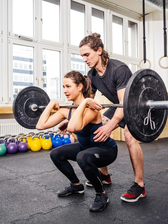 Photo of a young woman at a crossfit gym doing squats while her instructor watches from behind. Stock Photo