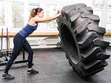 empujando: Foto de una mujer joven y atractiva que se resuelve con un neumático de tractor en un gimnasio CrossFit. Foto de archivo