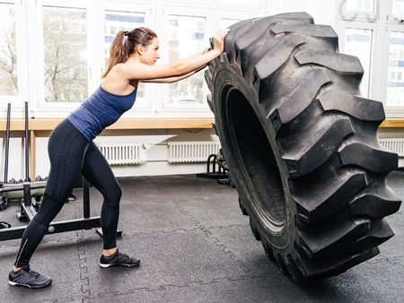 huge: Photo of an attractive young woman working out with a tractor tire at a crossfit gym.