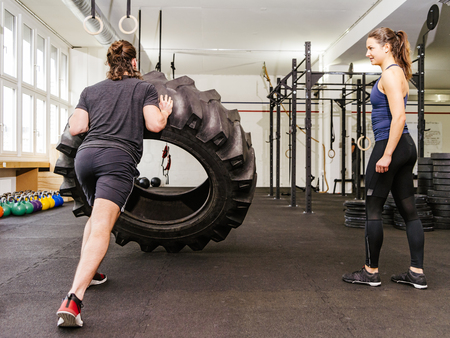 huge: Photo of an attractive young woman and man working out with a tractor tire at a crossfit gym.