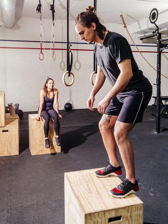 fitness hombres: Foto de una mujer joven y atractiva y el hombre trabajando haciendo saltos en un gimnasio CrossFit.
