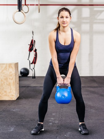 kettle bell: Photo of a young woman exercising with a kettle bell at a crossfit gym. Stock Photo
