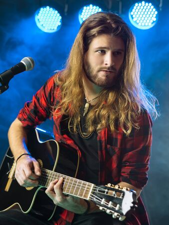 male hair: Photo of a young man with long hair and a beard playing an acoustic guitar on stage with lights and concert atmosphere.