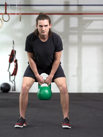 kettle bell: Photo of a young man exercising with a kettle bell at a gym. Stock Photo