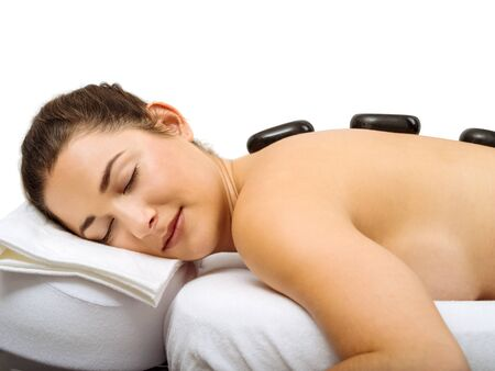 woman lying: Photo of a young woman lying in a spa having a hot stone treatment. Stock Photo