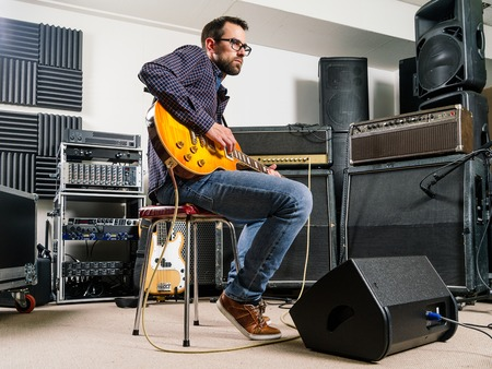 play room: Photo of a man in his late 20s sitting in a recording studio playing his electric guitar. Stock Photo